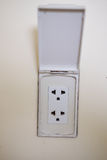 White plugs. Electric plug outlet on white wall stock images