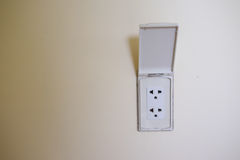 White plugs. Electric plug outlet on white wall stock photography