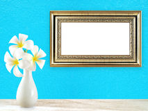 Beautiful pure white plumeria bouquet in simple white ceramic vase on wooden table floor and blank golden vintage picture frame. On bright blue concrete wall royalty free stock image