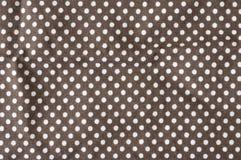 White polkadots on brown background. White polkadots printed on brown fabric Stock Photo