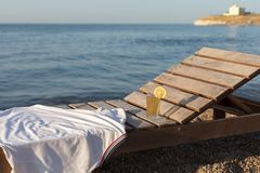 Sunbed with polo shirt and glass of cold drink on it at sea beach. White polo shirt and glass of cold drink on sunbed at pebble sea beach at dawn Royalty Free Stock Photography
