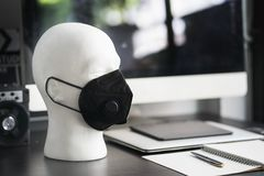 White Polystyrene Foam Male Display Mannequin Head wearing protection Dust mask,Various types of n95 or protect from PM2.5 on. Wooden desk with computer royalty free stock photo