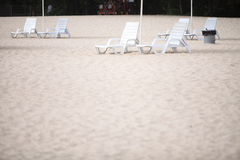 White pool chairs on sand beach Royalty Free Stock Image