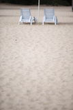 White pool chairs on sand beach Stock Image