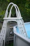 White pool ladder sitting in Pool in warm summer day royalty free stock image