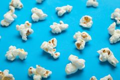 White popcorn on blue background. Flat lay pattern stock photos