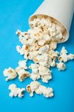 White popcorn scattered from a white paper bucket on a blue background royalty free stock photography