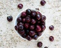 White porcelain bowl full of fresh cherries. On stone table Royalty Free Stock Photography