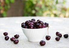 White porcelain bowl full of fresh cherries. On stone table Stock Photos