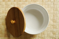 White porcelain bowl with lid. A white porcelain bowl with a wooden lid rests on place-mat Stock Images