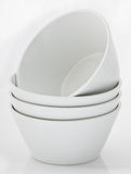 White porcelain bowls. On a seamless white background Stock Photos