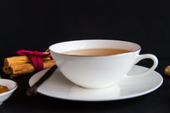White china tea cup over black background. White porcelain china tea cup over black background with marmalade and spices around it stock image