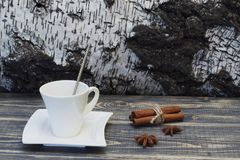 White porcelain coffee pair of unusual shape, sticks of fragrant cinnamon and a tart star anise on a natural wooden tabletop stock photos