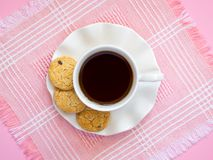 White porcelain cup with coffee and few oat cookies with pieces of dark chocolate on saucer with wavy edge on a pink table napkin. Sweet high-calorie breakfast stock photos