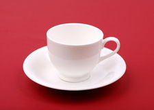 White porcelain cup on a red Stock Images