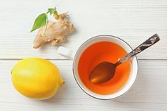 White porcelain cup, silver spoon, hot amber tea in, lemon and dry ginger root with green sprout next to it. Top view, wooden stock photos