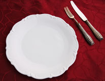 White porcelain dish, silverware on damask-cloth. For an elegant dinner: damask, porcelain and silverware royalty free stock images