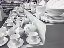 White porcelain dishes and cups stay on table stock photography