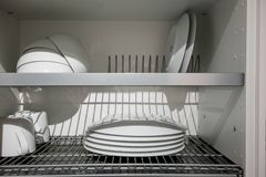White porcelain dishes dried on metal dish rack. Way to organize. Kitchen and minimize space with modern drainer in cabinet against white background Stock Photos