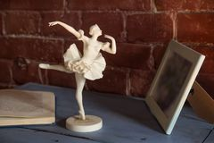 White porcelain figurine of a ballerina with an open book against Royalty Free Stock Photography