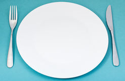 White porcelain plate with fork and knife on green Stock Image