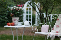 White porcelain set for tea or coffee on table in the garden over blur green nature background, shallow depth of field. Royalty Free Stock Image