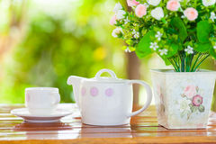 White porcelain set for tea or coffee on wooden table. In the garden over blur green nature background, shallow DOF teapot in focus royalty free stock images