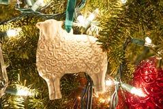 A white porcelain sheep folk art ornament on a Christmas tree. royalty free stock photos