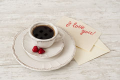 White porcelain tea set with cup of coffee and hearts. White porcelain tea set with cup of coffee, greeting card and couple small red hearts. Valentine's Stock Photo