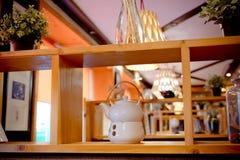 White porcelain tea set on a wooden shelf. Tea or coffee time. White ceramic tea set on a wooden shelf. White porcelain tea set on a wooden shelf. Tea or coffee stock photo