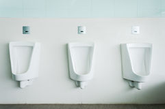 White porcelain urinals. Group of white porcelain urinals in public toilets Royalty Free Stock Photography