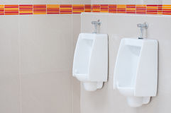 White porcelain urinals Stock Photos
