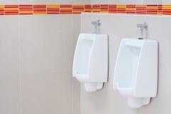White porcelain urinals Stock Photos