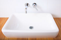 White porcelain washbasin and chrome-plated faucets. Stock Photography