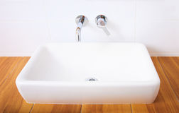White porcelain washbasin and chrome-plated faucets. Stock Image