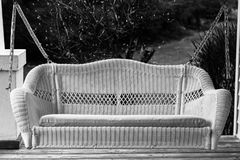 White porch swing. Black and white image of a white woven porch swing on chains Stock Photography