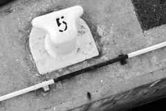 White port mooring bollard with number 5 Stock Image