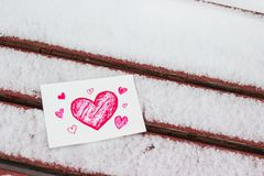 White postcard with a red painted heart lies on a wooden bench in February. White greeting card with a red painted heart in the hands, a declaration of love on stock image