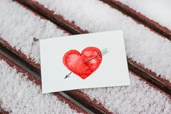 White postcard with a red painted heart lies on a wooden bench in February. White greeting card with a red painted heart in the hands, a declaration of love on stock photos