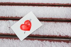 White postcard with a red painted heart lies on a wooden bench in February. White greeting card with a red painted heart in the hands, a declaration of love on royalty free stock photo