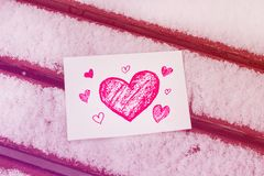 White postcard with a red painted heart lies on a wooden bench in February. White greeting card with a red painted heart in the hands, a declaration of love on royalty free stock images