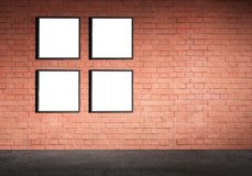 White poster in black frame mock up. Blank white paper poster in black frame at red brick wall and concrete floor. Grungy interior, poster mock up. Presentation Stock Images