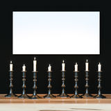 White poster on black wall illuminated a variety of candles. Moc Royalty Free Stock Photography