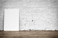 White poster on brick wall and wood floor Royalty Free Stock Image
