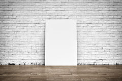 White poster on brick wall and wood floor Stock Images
