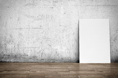 White poster on concrete wall and wood floor Royalty Free Stock Images