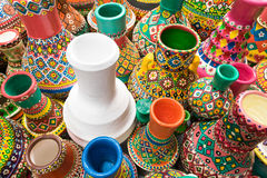 White pottery vase surrounded with collection of painted colorfu Royalty Free Stock Photo