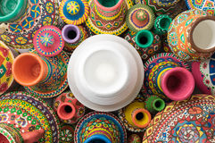 White pottery vase surrounded with collection of painted colorfu Royalty Free Stock Photography