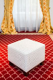 White pouf in the room with vintage red carpet and yellow drapes Stock Photos