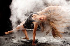 White powder dance pose. Dance expression of a female dancer in a cloud of white powder with her hair falling open Stock Image